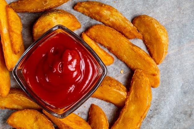 Деревенский жареный картофель на фоне бумаги с кетчупом. вид сверху.