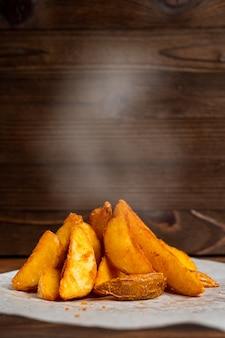 Деревенская зажаренная картошка на бумаге и деревянная предпосылка с дымом.