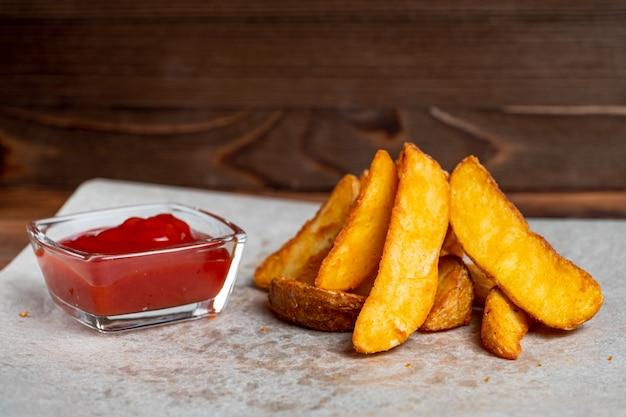 Деревенский жареный картофель на бумаге и деревянный фон с кетчупом.