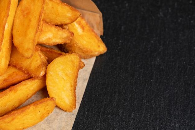 Деревенский картофель на грифельной посуде, черный камень.