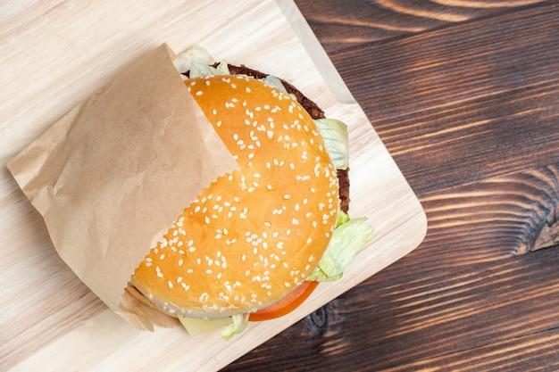 Бургер в бумаге и на световом табло сожгли деревянный вид сверху