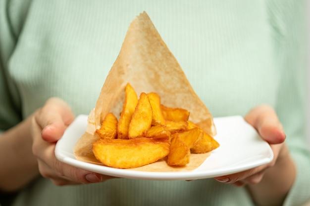 Девушка держит тарелку с деревенской картофелем в бумаге.