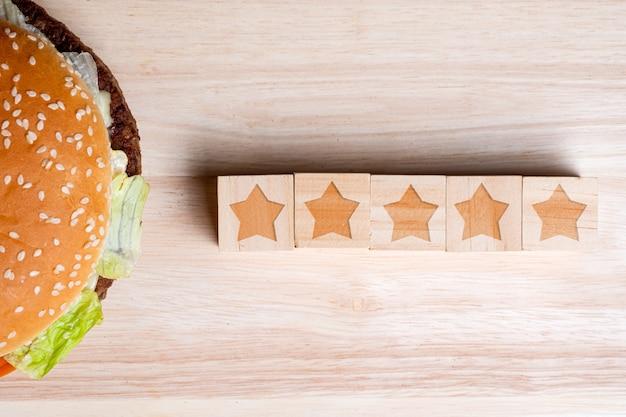 Бургер с звездами иконы на фоне деревянные. концепция рейтинга.