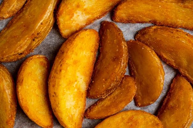 Деревенская жареная картошка на фоне бумаги. вид сверху.