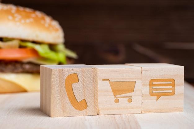 Бургер с иконами покупки контактов и сообщений на деревянном фоне.