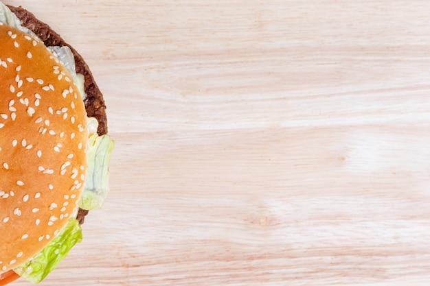 Взгляд сверху бургера на деревянной предпосылке. копировать пространство