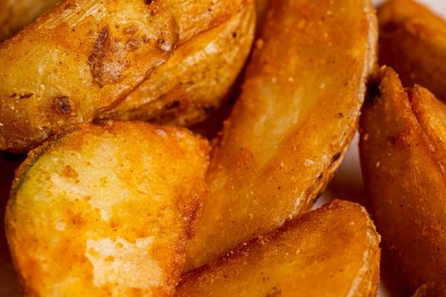 Деревенская зажаренная картошка в конце-вверх на бумажной предпосылке.