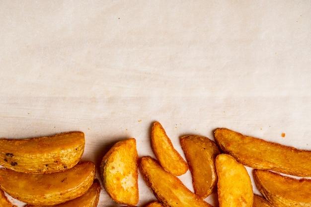 Деревенский жареный картофель на фоне бумаги. копировать пространство