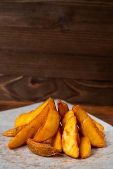 Деревенский жареный картофель на бумаге и деревянных фоне.