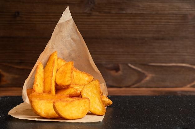 Картофель деревенский посуда шифер, черный камень на деревянном фоне. закройте