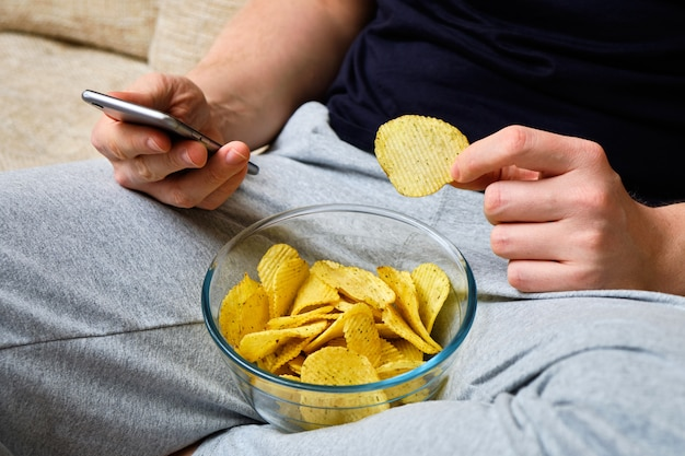 Мужчина сидит на диване, использует смартфон и ест чипсы.