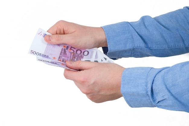 Рука в голубой рубашке держать банкноты евро на белом фоне. изолированные.