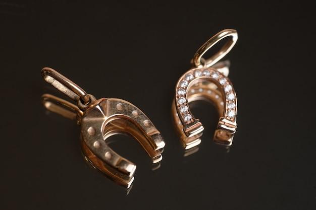 Золотые серьги в форме подковы на стекле.