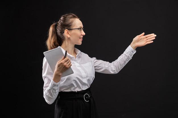 ノートを押しながら黒い背景に彼の手で指している白いシャツの女の子。
