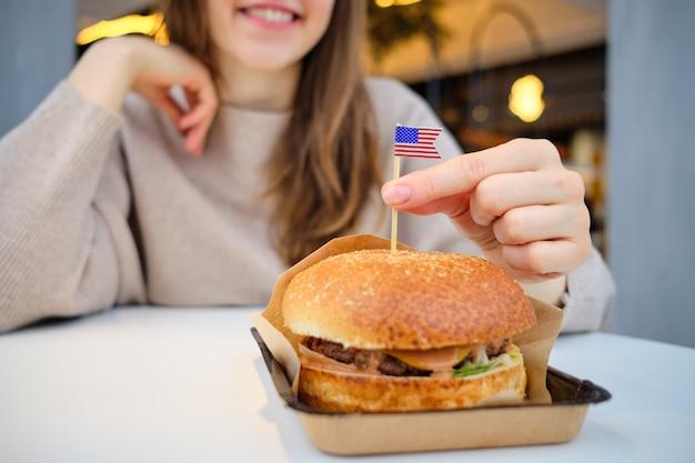 Бургер в крафт-бумаги на столе с флагом сша и девушка смотрит с аппетитом.