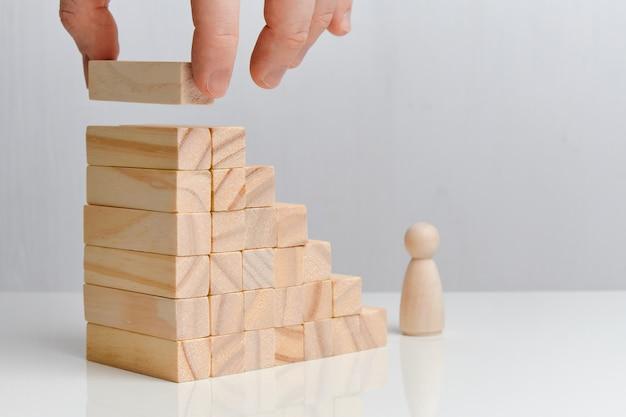手は階段を作る木製のブロックを保持します