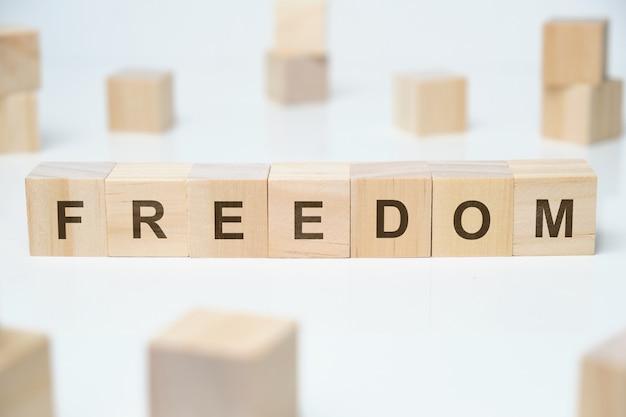 白い背景の上の木製のブロックに自由という言葉