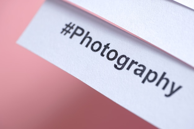 Популярный хэштег «фотография» напечатан на белой бумаге на розовом