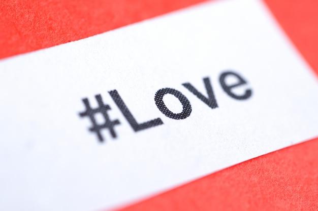 Популярный хэштег «любовь» напечатан на белом листе бумаги на красном