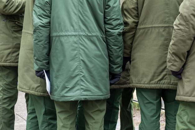 Несколько солдат стоят и разговаривают в городе в теплой военной одежде.