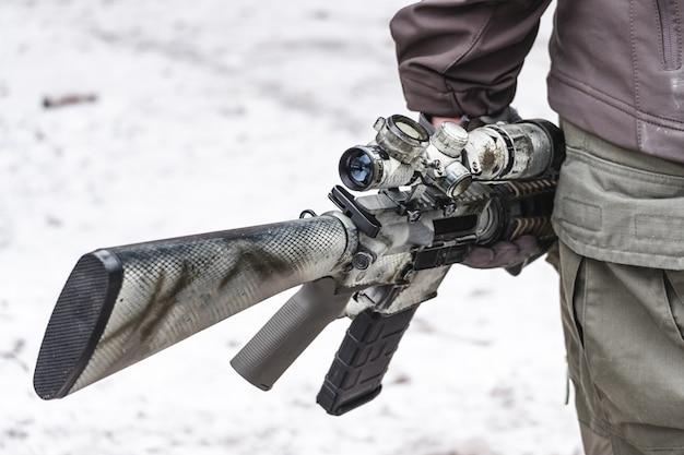 Военные несут винтовку с прицелом.