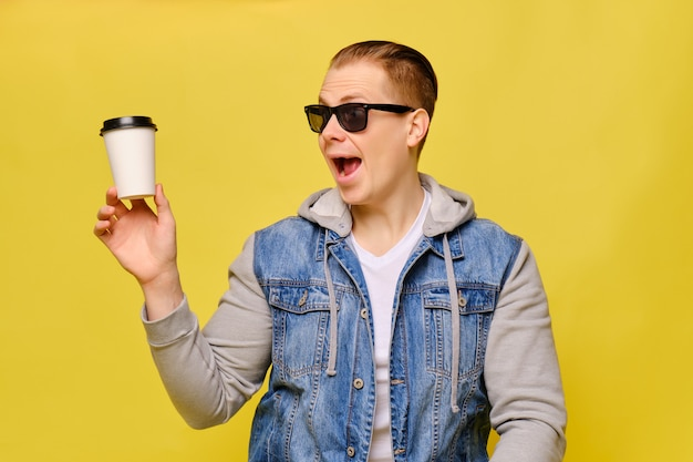 Стильный мужчина кавказской в джинсы и солнцезащитные очки на желтом фоне. рука демонстративно держит одноразовый бумажный стаканчик для кофе и смотрит на него.