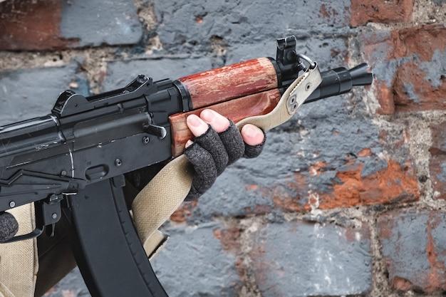 Наемный солдат целится из современной винтовки возле кирпичной стены.