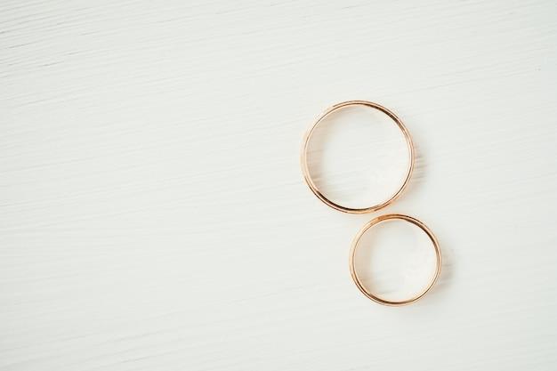 Обручальные золотые кольца лежат рядом друг с другом в правой части на белом фоне.