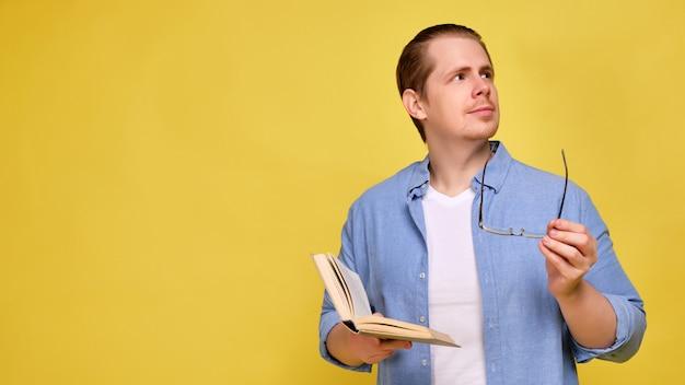 にシャツの男はメガネと本を保持し、側に見えます。場所をコピーします。
