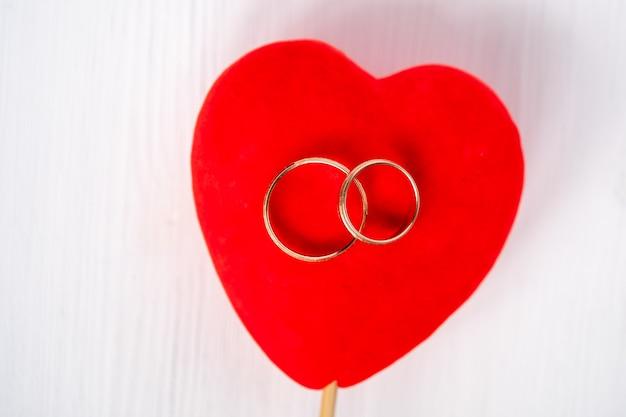 白い背景の上の赤いベルベットのハートのペア結婚金の指輪。オーバーヘッドショット