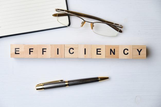 現代のビジネス流行語-効率。ブロックと木製のテーブルの上から見る。上面図。