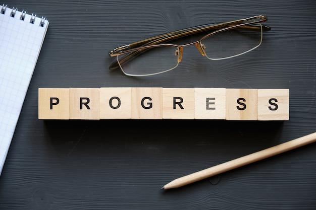 現代のビジネス流行語-進歩。ブロックと木製のテーブルの上から見る。上面図。