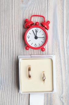 Золотые обручальные кольца в подарочной коробке с красными часами. вид сверху.