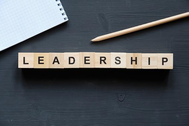 現代のビジネス流行語-リーダーシップ。ブロックと木製のテーブルの上から見る。上面図。