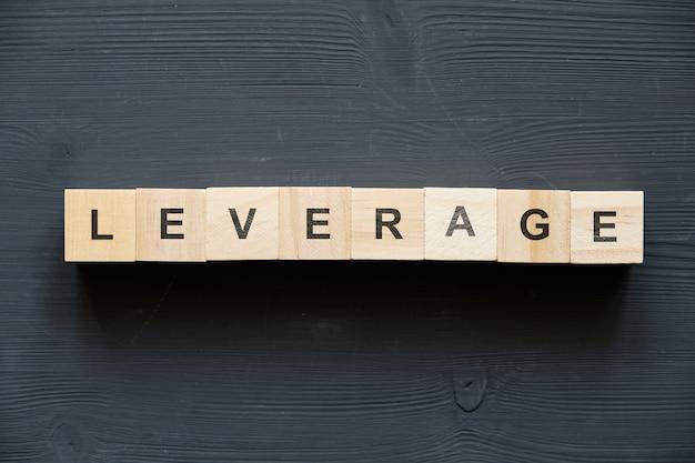 現代のビジネス流行語-レバレッジ。ブロックと木製のテーブルの上から見る。上面図。