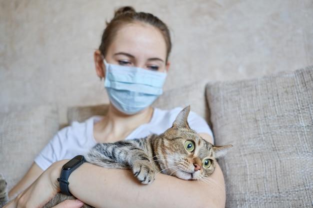医療用マスクを着た女の子は自宅で隔離され、猫の世話をしています。