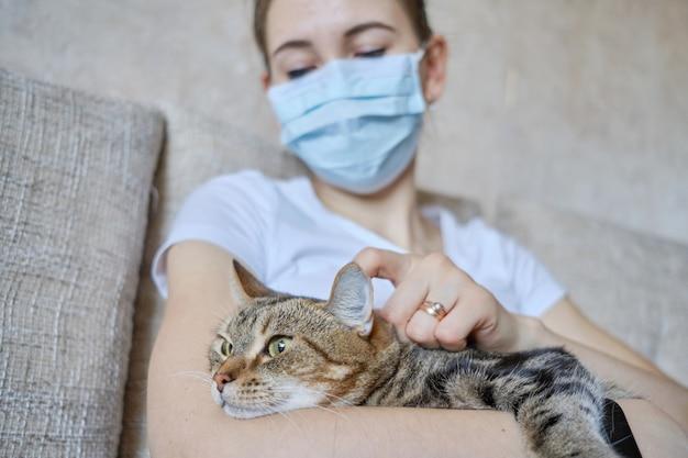 医療用マスクを着た女の子は自宅で孤立し、猫の耳の後ろを引っ掻いています。
