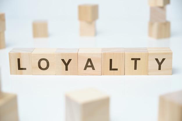 現代のビジネス流行語-忠誠心。空白の木製のブロックの単語。