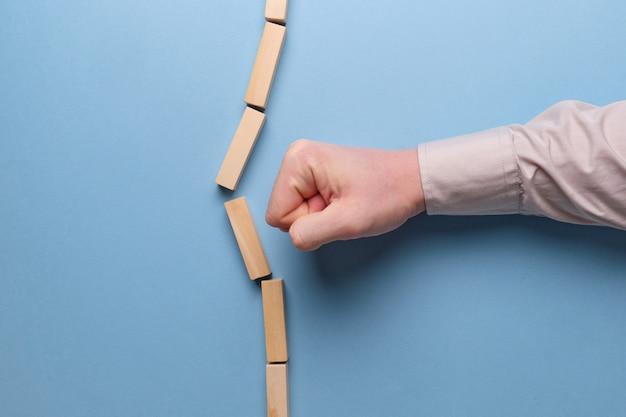 ステレオタイプを壊すという概念。手は青い空間に木製のブロックを保持しています。