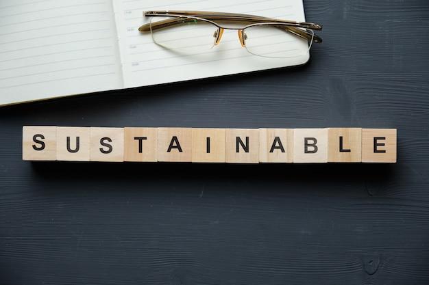 現代のビジネスの流行語-持続可能な。ブロックと木製のテーブルの上から見る。上面図。