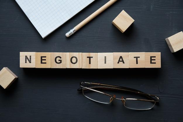 現代のビジネス流行語-交渉。ブロックと木製のテーブルの上から見る。上面図。