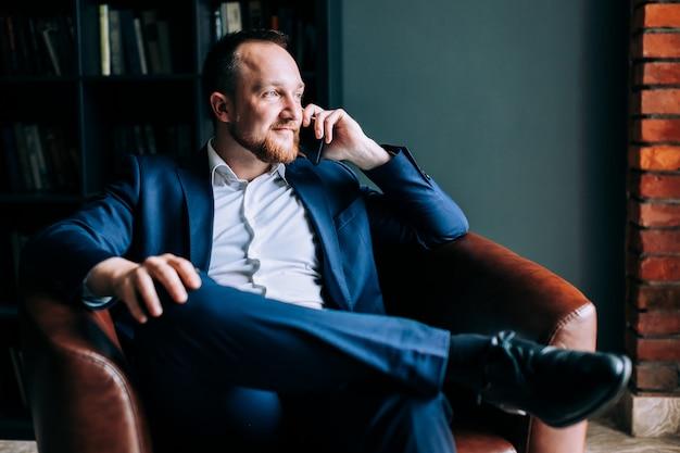 スーツで成功した実業家は、トレンディなオフィスの椅子に座って、窓の外に見えます。