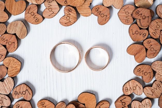 白い背景の上の木の心に囲まれたペアの結婚式の金の指輪。オーバーヘッドショット