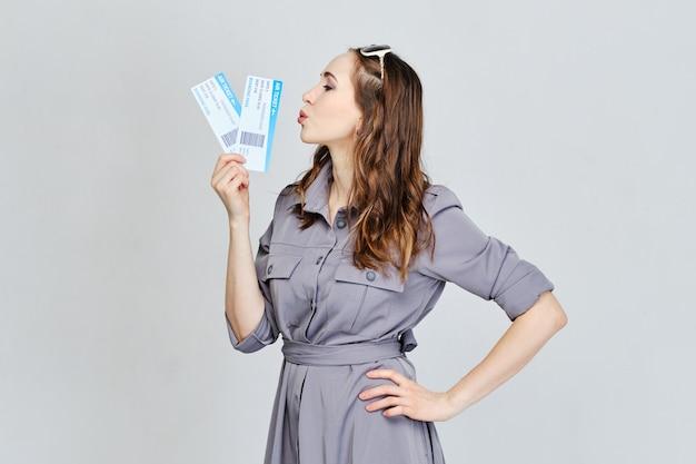 女の子は旅行の概念として飛行機のチケットにキスします。