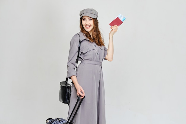 少女は飛行機のチケットでパスポートを保持し、荷物を持って上陸に行きます。