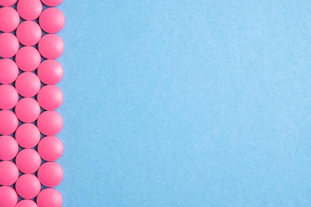 青色の背景の両側にピンクの錠剤の行。コピースペース。