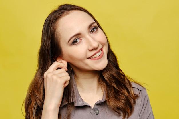 美しい白人少女の肖像画は、黄色の背景に灰色のドレスを着た耳に触れます。