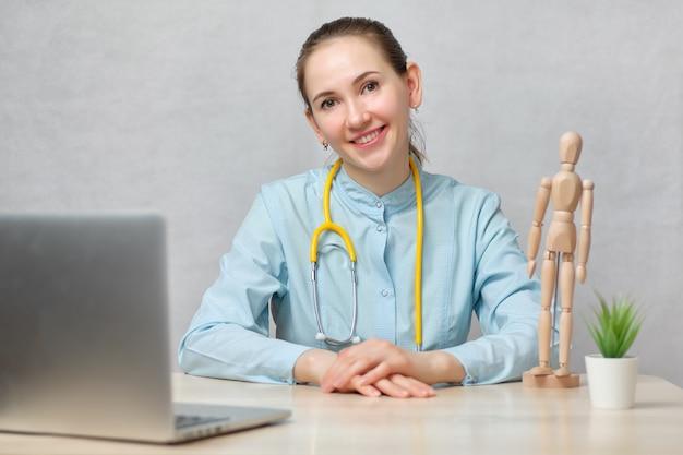 女の子医師セラピストは白い背景の上のラップトップでテーブルに座っているし、カメラを見てください。