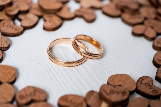 Пара золотых обручальных колец, обрамленная деревянными сердечками на белом фоне. вид сбоку.