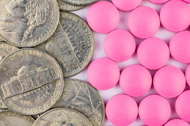 コイン上面とピンクの丸薬。閉じる。医薬品ビジネスでの成功。